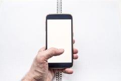 Hand die en mobiele smartphone houden gebruiken Stock Fotografie