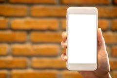 Hand die en witte mobiele telefoon met het lege Desktopscherm houden opheffen met bakstenen muurachtergrond Stock Fotografie