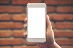Hand die en witte mobiele telefoon met het lege Desktopscherm houden opheffen met bakstenen muurachtergrond Royalty-vrije Stock Foto's