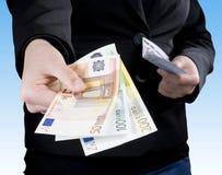Hand, die Eurobanknotegeld führt Stockfoto