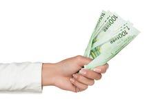 Hand, die Eurobargeld anhält Stockfoto