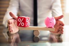Hand die Evenwicht tussen Percentage en Piggybank beschermen royalty-vrije stock foto