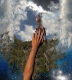 Hand, die für Sicherheits-Hilfe in den Wolken erreicht Stockbilder