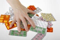 Hand, die für Tabletten erreicht Stockfoto