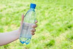 Hand die fles water aanbiedt Royalty-vrije Stock Foto's