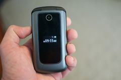 Hand, die Flip Phone Feature Phone hält Stockfotos