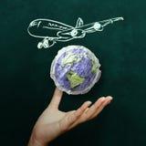 Hand, die Flugzeug mit zerknittertem Weltpapier zeigt Stockfotos