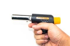 Hand, die Gaskochenflammenwerfer lokalisiert hält Stockfotografie