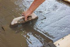 Hand die gegoten concreet en nivellerend beton uitspreiden royalty-vrije stock afbeeldingen