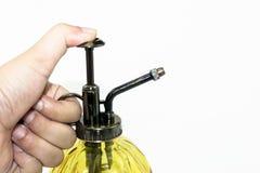 Hand, die gelbes Sprayglasflaschenisolat drückt Lizenzfreie Stockfotos