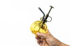 Hand, die gelbes Sprayglasflaschenisolat hält Stockfoto