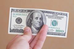 Hand, die Gelddollar anhält Lizenzfreie Stockbilder