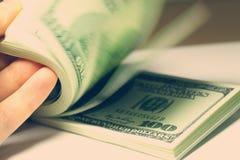 Hand, die Gelddollarnahaufnahme zählt Stockbild