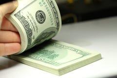 Hand, die Gelddollarnahaufnahme zählt Stockfotos