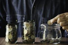 Hand die geldmuntstuk in de glaskruik zetten Besparingsgeld, financiële en boekhoudingsconcept royalty-vrije stock fotografie