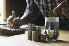 Hand die geldmuntstuk in de glaskruik zetten Besparingsgeld, financiële en boekhoudingsconcept royalty-vrije stock foto