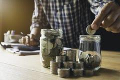 Hand die geldmuntstuk in de glaskruik zetten Besparingsgeld, financiële en boekhoudingsconcept stock fotografie