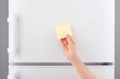 Hand die gele kleverige document nota over witte ijskast houden Royalty-vrije Stock Afbeeldingen