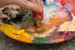 Hand die gele oilpaint op palet drukt Royalty-vrije Stock Afbeelding