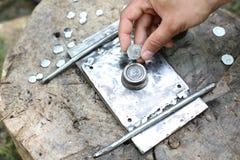 Hand, die geprägte römische Münze auf einem Prägungsgerät hält stockbilder