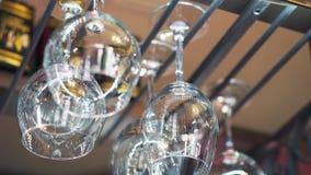 Hand die gewassen glazen toevoegen aan een glaswerkhouder in een bar stock footage