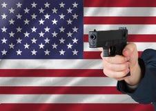 Hand, die Gewehr mit amerikanischer Flagge hält Stockfotos
