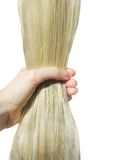 Hand, die glänzendes langes blondes Haar aufträgt Stockfotografie