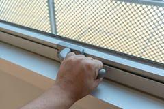Hand, die Glasfenster-Verriegelungsgriff h?lt stockfotografie