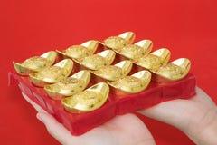 Hand, die Goldbarren für Feier des Chinesischen Neujahrsfests gibt Stockfotos