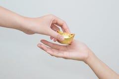 Hand, die Goldbarren für Feier des Chinesischen Neujahrsfests gibt Lizenzfreie Stockfotografie