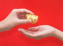 Hand, die Goldbarren für Feier des Chinesischen Neujahrsfests gibt Lizenzfreies Stockfoto