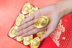 Hand, die Goldbarren für Feier des Chinesischen Neujahrsfests gibt Lizenzfreie Stockbilder