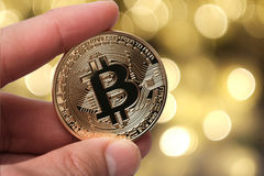 Hand, die goldenes bitcoin auf abstraktem Hintergrund hält Stockfoto