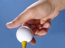 Hand, die Golfball auf T-Stück setzt Lizenzfreies Stockbild