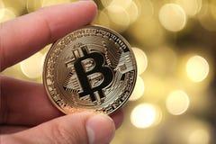 Hand die gouden bitcoin op abstracte achtergrond houden stock foto