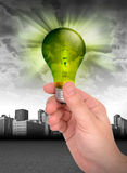 Hand, die grüne Energie-Glühlampe anhält stockbild
