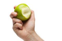 Hand, die grünen Apfel mit Bissenvermißten anhält lizenzfreie stockfotografie