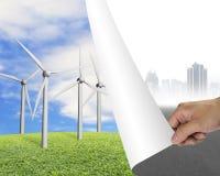Hand die grijze cityscape pagina draaien die groep windturbine openbaren Stock Foto