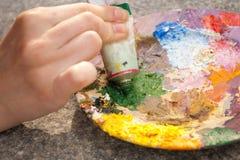 Hand die groene oilpaint op palet drukt Royalty-vrije Stock Foto's
