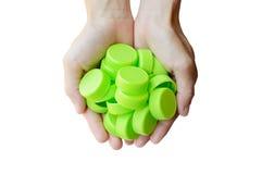 Hand die groene plastic kroonkurk op witte achtergrond houden Royalty-vrije Stock Afbeeldingen
