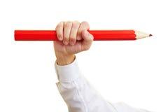 Hand die groot rood potlood houdt Royalty-vrije Stock Afbeeldingen