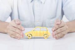 Hand, die hölzerne Autoversicherung hält KonzeptUnfallverhütung Stockbild