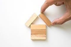 Hand, die hölzernen Block als Haus vereinbart Stockbilder