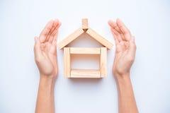Hand, die hölzernen Block als Haus vereinbart Lizenzfreie Stockfotografie