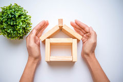 Hand, die hölzernen Block als Haus vereinbart Lizenzfreie Stockbilder