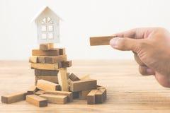 Hand, die hölzernen Block mit vorbildlichem weißem Haus auf Spiel des hölzernen Blockes hält Anlagerisiko und Ungewissheit im Imm stockfotos