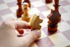 Hand, die hölzernes Schachspiel auf Schach Brett hält Schach Schwarzes und W stockfoto