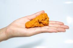 Hand, die Hühnerflügel hält Lizenzfreie Stockbilder
