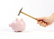 Hand, die Hammer und umgedrehtes rosa Sparschwein hält Lizenzfreie Stockfotografie
