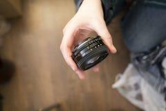 Hand die hand eerste lens 50 mm op donkere achtergrond houden Stock Fotografie